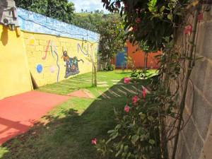 Área lateral ao acesso chegando na varanda aberta no jardim.