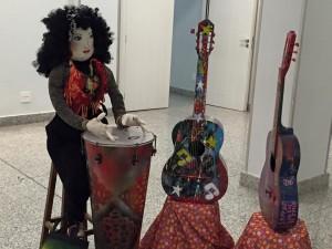 Os tambores e violões representam as oficinas de Música.